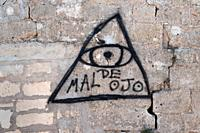 "A graffiti """"evil eye"""" painted by a gypsy on a wall in the South of France."