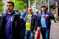 A group of men walk together through the shopping streets of Hamburg.