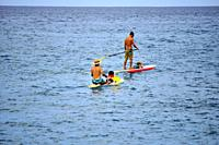 Two men with children on paddle boards, Hawaii, Big Island, USA.