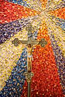 Crucifix of Jesus of Nazareth King of the Jews on brass standard with starburst mosaic tile backdrop in a Roman Catholic church Toronto Ontario Canada...