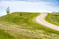 Canada, Alberta, Turner Valley. Curving dirt road reaching the crest of a hill in the foothills of the Rocky Mountains