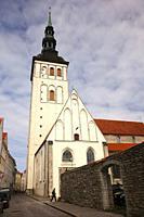 Man in front of the Niguliste Church-Niguliste Kirik dedicated to St. Nicholas in the old town, Tallinn, Estonia, Baltic States, Europe