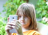 Boy with Blond Hair Looking at Mobile Phone.