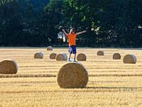 Boy Climbing a Bale of Hay on a Field in Summer.