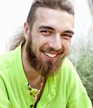 Portrait of a Teenage Boy with Long Hair and Beard Outdoors.