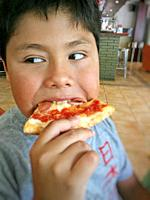 Boy eating a pizza.