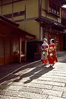 Two young Maiko, Geisha apprentices in bright kimono walking down on an old street in Higashiyama, Kyoto, Japan.