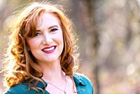 Portrait of a smiling 27 year old redhead woman outdoors.