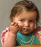 two-year old learning to feed herself from the bowl usoing a teaspoon. Cape Town, South Africa.
