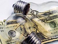 A lightbulb on dollar bill, energy saving concept.
