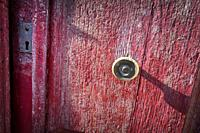 Close-up of the knob of an old door with flaking red paint. Santo-Pietro-di-Tenda, Corsica, France.