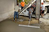 Work crew pouring cement from a cement truck shute over wire mesh on a residential garage floor and spreading with large float trowel and rake Toronto...