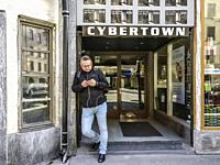Sweden, Stockholm. Sankt Eriksplan, Man with mobile phone in front of Cybertown gaming hall.