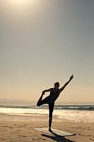 A young woman is exercising a stand up yoga pose at a beach.
