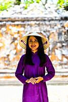Vietnamese woman wearing the traditional ao dai costume in the Imperial City, a walled palace within the citadel of the city of Hue, which is the form...