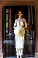 Vietnamese women wearing the traditional Ao Dai costume walking in the Imperial City, a walled palace within the citadel of the city of Hue, which is ...