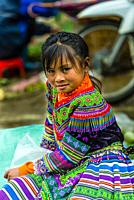 Flower Hmong (hill tribe) girl at the Sunday market at Bac Ha, northern Vietnam. Every Sunday ethnic minorities gather to buy and sell everything from...