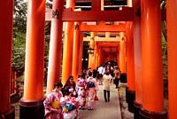 Tourists and women in kimono walking along a long Torii path, Senbon torii, a row of orange gates, at Fushimi Inari Taisha head shrine in Fushimi Ward...