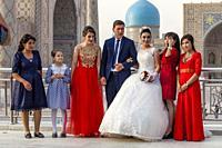 A â. . Just Marriedâ. . Young Couple Pose For Wedding Photos At The Registan Complex, Samarkand, Uzbekistan.