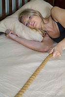 Teenage blonde girl lying in her bed, pulling on a rope.