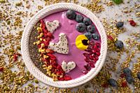 Acai bowl smoothie pitaya hearts blueberry goji chia pomegranate and seeds for Valentines day.