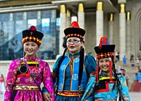 Three young women pose in traditional deel costume and the typical hat with the cone shaped top, Mongolian National Costume Festival, Ulaanbaatar, Mon...