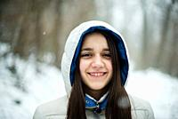 portrait of an 11-year-old girl outside under a snowfall, in a forest, dressed in a down jacket, a windbreaker.