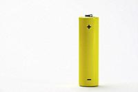 Yellow battery on a white table.