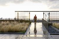 Seattle, Washington: Man walk laps on the Russell Investment Center Observation Deck as a rainstorm passes. The 25,000 square foot terrace on the buil...