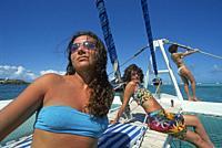 young women sunbathing on a sailing catamaran, Tobago Cays, Grenadines islands, Saint Vincent and the Grenadines, Winward Islands, Lesser Antilles, Ca...