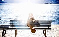 Woman Sitting on a Bench on the Waterfront and Looking Back with Sun Reflection in Ascona, Switzerland.