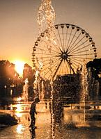 Child Playing in the Water Fountain with Ferris Wheel in Background in Sunset in Nice, France.
