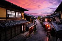 Beautiful sunrise scenery of Yasaka dori historic street in Kyoto empty and quiet in early morning with colorful dramatic red purple sky and shining s...