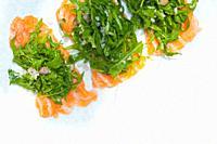 fresh salmon carpaccio sushi sashimi with arugula rocket salad and caper on top.