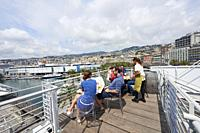 People enjoying an outdoor meal overlooking the Old Port area. Genoa. Italy.