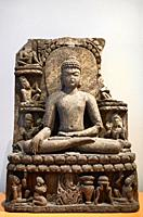 Seated Buddha stone sculpture at enlightenment touching the ground surrounded by Bodhasittvas and above worshipping devotees at ROM Toronto Canada