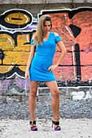 Sensual, beautiful, attractive Ukrainian woman wearing a blue dress posing near a graffiti painted wall for a photographic sequence in Yalta, Crimea.