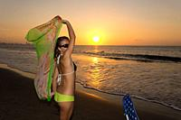 Happy beautiful blonde woman with a beautiful body posing standing next to a beach chair in a sequence of pictures at the sunset in Cartagena Colombia...