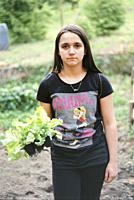 portrait of teenager with salad seedling in hand in the vegetable garden, ready to be planted.