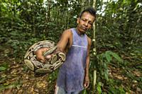 Local guide with a red-tailed boa constrictor, Boa constrictor constrictor, Landing Casual, Loreto, Peru.