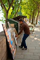 Traditional books and gifts seller (bouquiniste) organizing the display of his products next to the banks of the Seine. Paris, France.