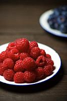 Close up of a raspberries group on a wood table.