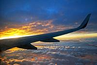 The wing of a plane flying above the clouds over a spectacular sunset at 10000 meters.