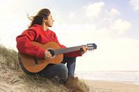 Woman playing her guitar at the beach. Tarifa, Costa de la Luz, Cadiz, Andalusia, Spain.