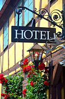 Hotel facade with roses, lamp and sign at an old house in Ystad, Scania, Sweden.