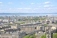 View on the roofs of the city of Edinburg and the sea in Scotland