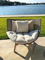 Chair in patio in fron of water, Key Biscayne, Florida, USA.