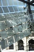 Glass and stainless steel light deflectors flutter like bunting on the facade of the Roman Museum at Nimes to reveal the massive stone arches of the R...