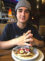 Young Man sitting in restaurant eating pancakes