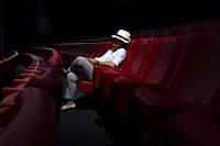 Woman with Hat Sitting Alone in Movie Theater.
